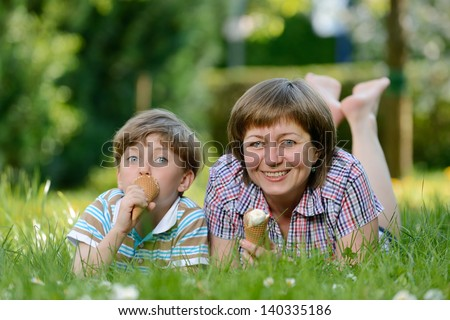 Happy family eat ice cream on a grass outdoors in spring park - stock photo