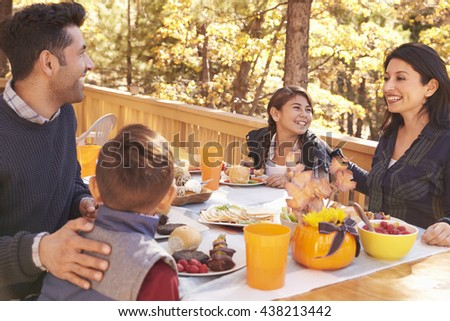 Happy family eating at table on a deck in a forest - stock photo