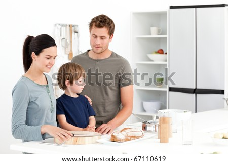 Happy family eating bread in the kitchen at home - stock photo