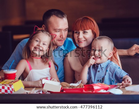 Happy family eating fast food in restaurant all together