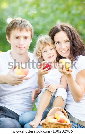 Happy family eating fruits outdoors in spring park against green background. Healthy lifestyle concept - stock photo