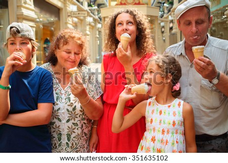Happy family eating ice cream walking through shopping mall  - stock photo