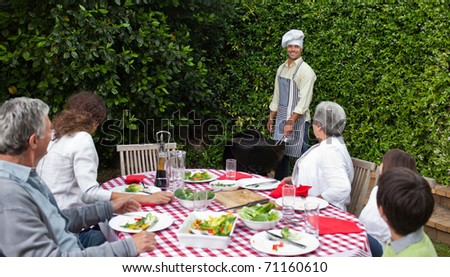 Happy family eating in the garden - stock photo