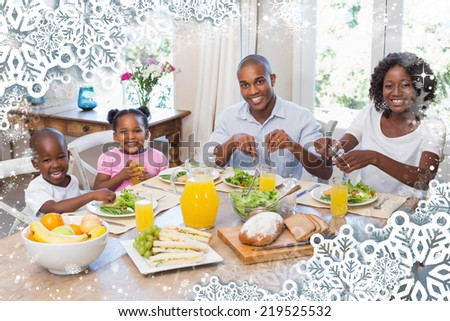 Happy family enjoying a healthy meal together against snow - stock photo