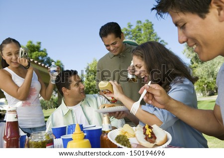 Happy family enjoying food while woman photographing them at park - stock photo