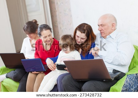 Happy family enjoys on sofa in livingroom with few laptops at home - stock photo
