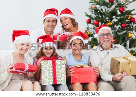 Happy family exchanging gifts at christmas time on the couch - stock photo