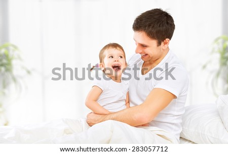 Happy family father and baby child daughter playing in bed - stock photo