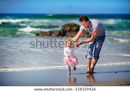 happy family father and baby girl daughter have a fun on a paradise beach ocean background - stock photo