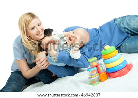 Happy family: father and baby lying down, playing and smiling - stock photo