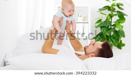happy family father and baby playing on bed - stock photo