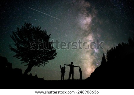 Happy family father and boys silhouette with Milky Way and beautiful night sky full of stars in background - stock photo