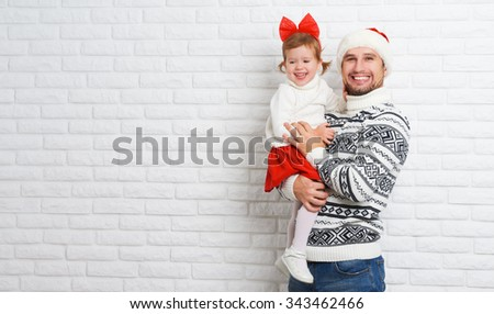 Happy family father and child with a gift in a Christmas from a blank brick wall - stock photo