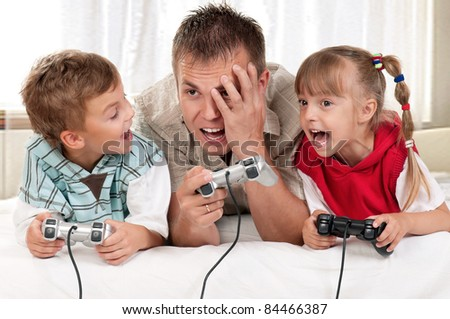Happy family - father and children playing a video game - stock photo