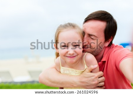 Happy family father and his adorable little daughter at beach making selfie - stock photo