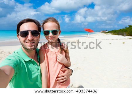 Happy family father and his adorable little daughter at beach taking selfie