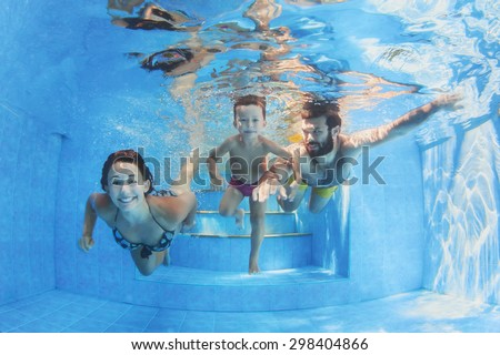 Happy family - father and mother with baby boy swimming and diving underwater with fun in blue pool. Healthy lifestyle, active parents, and people water sports activity on summer vacation with child - stock photo