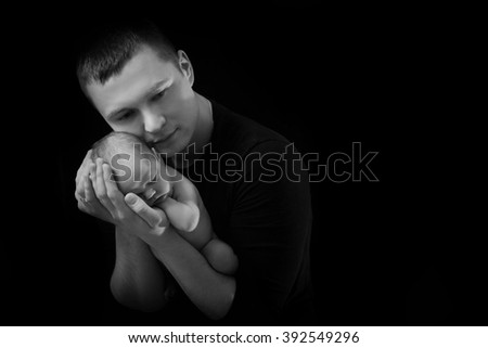 happy family , father holding a newborn baby in her arms daughter , who is asleep and gently hugged him, black and white photo on a black background , a lot of affection and love .