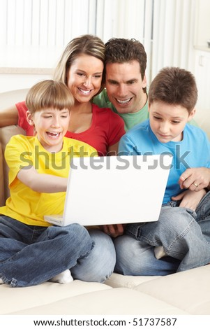 Happy family. Father, mother and boy working with laptop. - stock photo