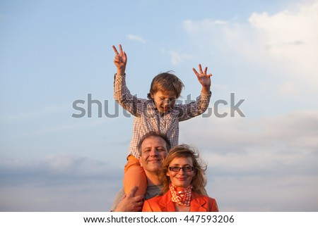 Happy family: father, mother and son have fun outdoor