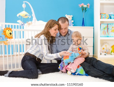 Happy family (father, mother and 1 year old baby girl) playing together at home, sitting on floor in children's room, smiling. Toys are officially property released.
