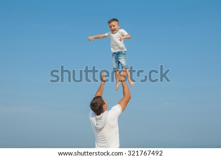 Happy family. Father throws up child in the sky, on sunny day. Father and little son on the beach. Positive human emotions, feelings, emotions. - stock photo