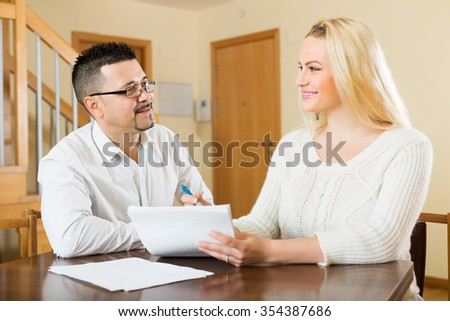 Happy family filling questionnaire for employee with laptop of the bank at home - stock photo
