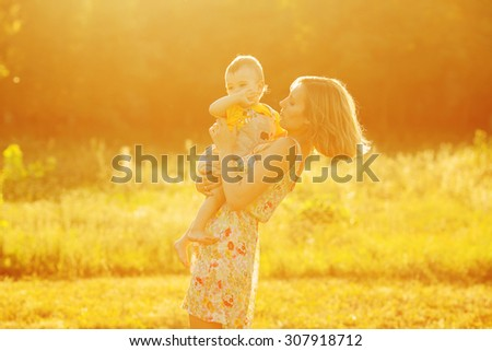 Happy family, friends forever concept. Profile portrait of mother and little son playing together in park. Mom holding baby. Sunny summer day. Vintage country style. Copy-space. Outdoor shot - stock photo
