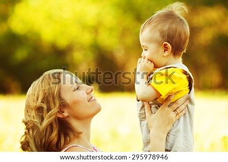 Happy family, friends forever concept. Smiling mother and little son playing together in a park. Mum holding baby. Sunny windy summer day. Close up. Copy-space. Outdoor shot - stock photo