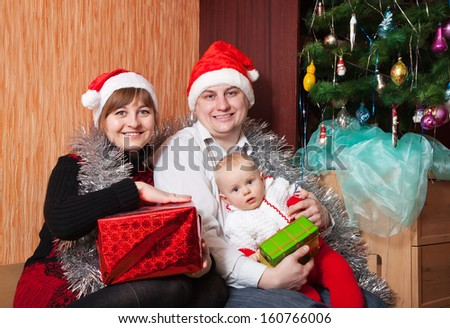 Happy family from 3 at  home with spruce - stock photo