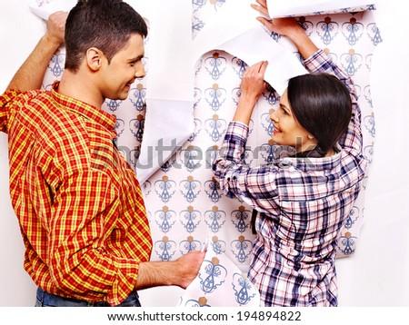 Happy family glues wallpaper at home. - stock photo