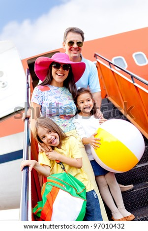 Happy family going on holidays by airplane - stock photo