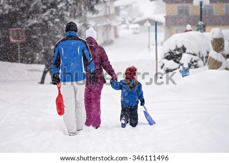Happy family, going out wintertime to slide, family fun outdoor - stock photo