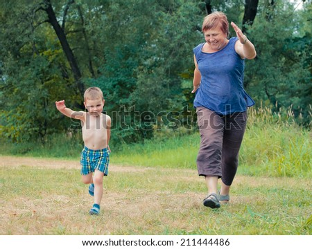 Happy family  grandmother and grandson  running  in the park