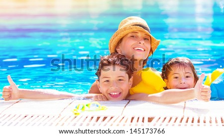 Happy family have fun in the pool, relaxation in aqua park, mother with two cute kids swimming in cool water, spending together summer vacation