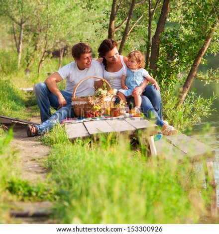 Happy family have picnic on the lake - stock photo