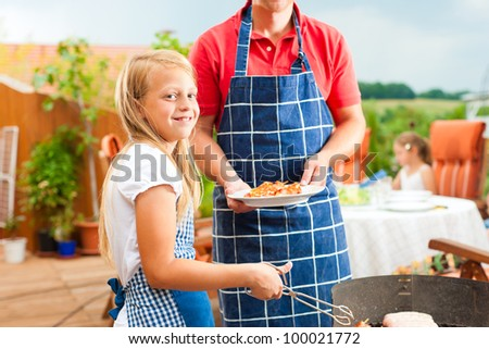 Happy family having a barbecue in summer; the father and a child standing at the grill - stock photo