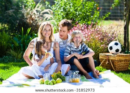 Happy family having a picnic in a park - stock photo