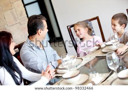 Happy family having dinner in the dinning room - stock photo
