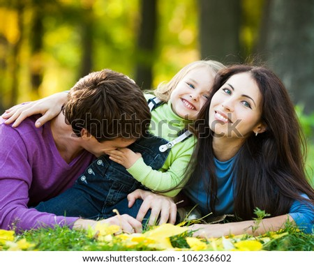 Happy family having fun against blurred autumn leaves background - stock photo