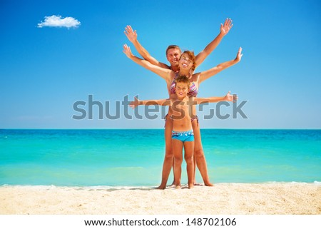 Happy Family Having Fun at the Beach. Joyful Family. Vacation and Travel concept. Summer Holidays. Parents with Child enjoying a holiday at the sea - stock photo
