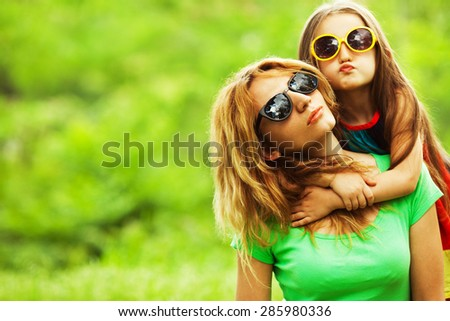 Happy family having fun. Baby girl with long brown hair and her mother with blond hair in trendy eyewear hugging each other. Close up. Copy-space. Outdoor shot