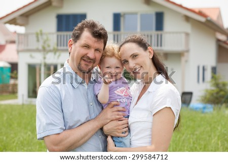 Happy family having fun in front of house - stock photo