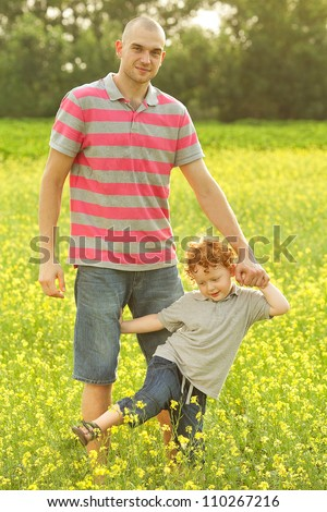 happy family having fun in the field with yellow flowers. Father holding his son and smiling. outdoor shot - stock photo
