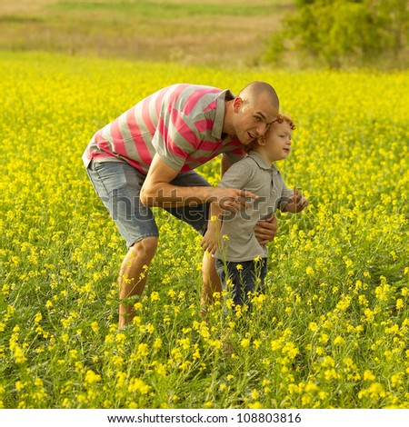 happy family having fun in the field with yellow flowers. Father showing something to his son. outdoor shot - stock photo