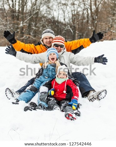 Happy family having fun in the snow - stock photo