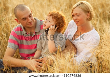 happy family having fun in the wheat field. Father and mother behind their son. Baby is calling on mobile (cell) phone. outdoor shot - stock photo