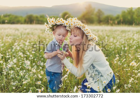 happy family having fun, mother holding him. outdoor shot. - stock photo