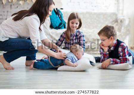 Happy family having fun on floor of in living room at home - stock photo