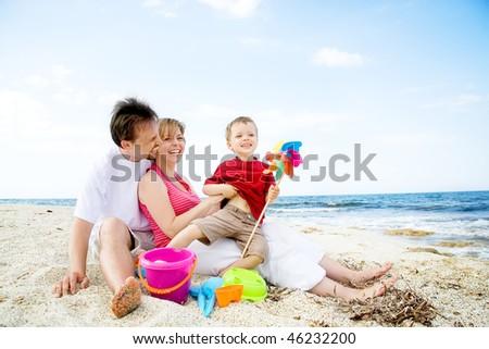 Happy family having fun on the beach. - stock photo